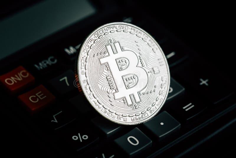 Bitcoin silvermynt på räknemaskintangentbordet Faktiskt cryptocurrencybegrepp royaltyfri bild