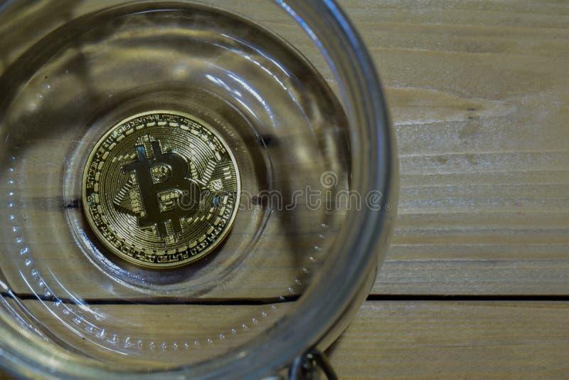 Bitcoin som är guld- i en krus på trätabellbakgrund Besparingar eller affärsidé royaltyfri foto
