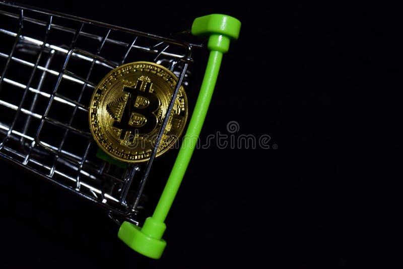 Bitcoin som är guld- i en shoppa vagn på svart bakgrund Köp- och försäljningsaffärsidé arkivbild