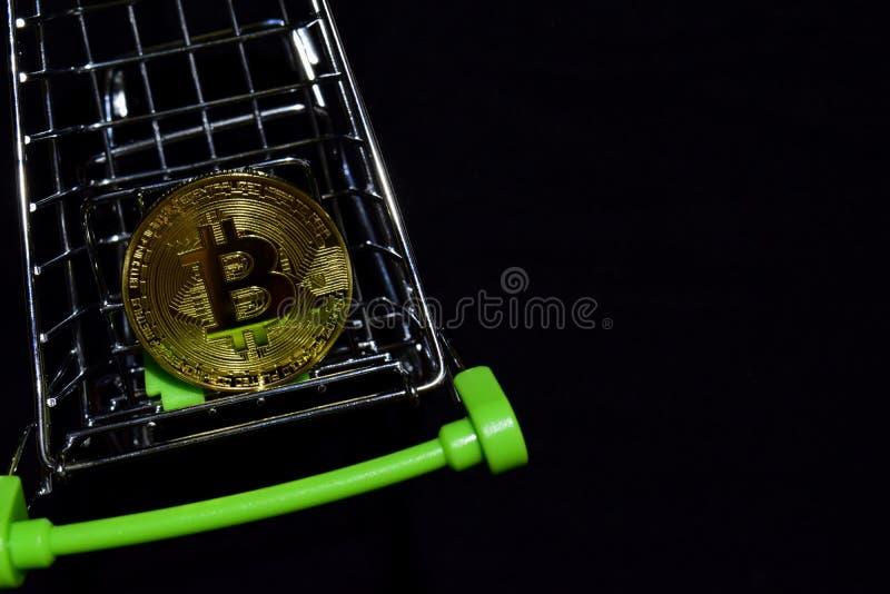 Bitcoin som är guld- i en shoppa vagn på svart bakgrund Köp- och försäljningsaffärsidé royaltyfri foto