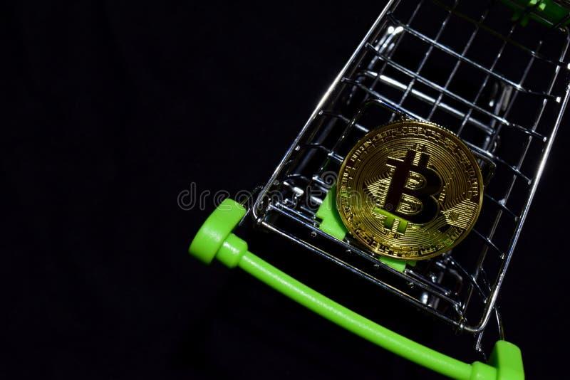 Bitcoin som är guld- i en shoppa vagn på svart bakgrund Köp- och försäljningsaffärsidé arkivbilder