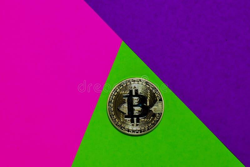 Bitcoin som är guld- på rosa, purpurfärgad och grön färgrik bakgrund fotografering för bildbyråer