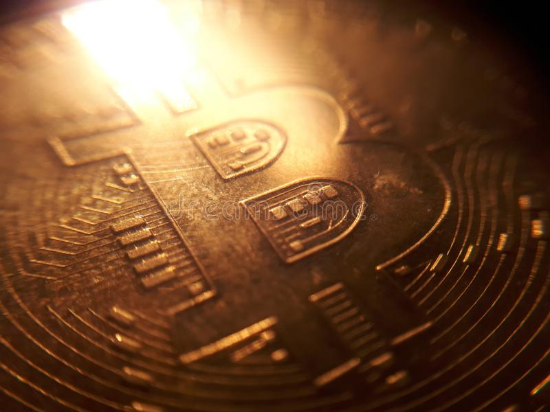 Bitcoin stack in blurry close-up shot with flames reflection stock photo