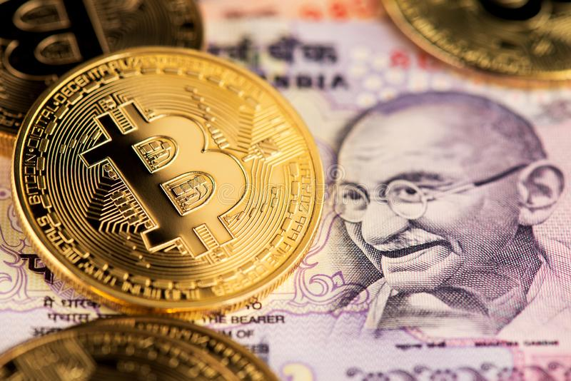 Golden Bitcoin cryptocurrency with Indian Rupee banknotes. Bitcoin on India Rupee Cryptocurrency against money from India. stock photography