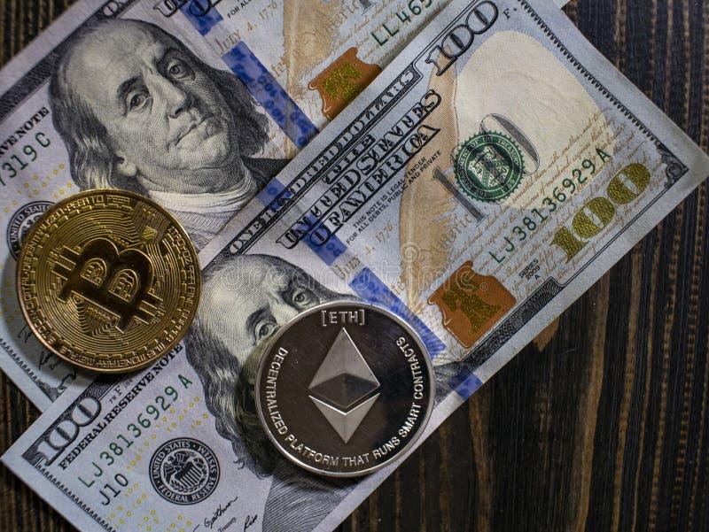 Bitcoin y Ethereum en los billetes de banco de cientos d?lares en un fondo de madera Imagen conceptual para el cryptocurrency mun fotos de archivo