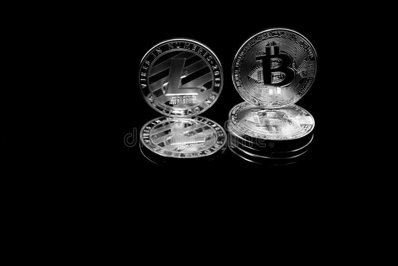 Bitcoin y litecoin Crypto de las monedas en un fondo negro imagen de archivo libre de regalías