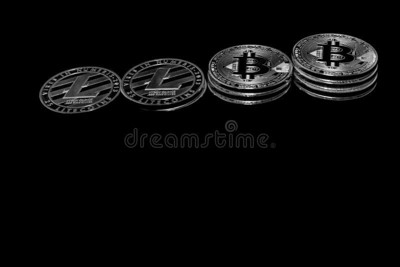 Bitcoin y litecoin Crypto de las monedas en un fondo negro foto de archivo