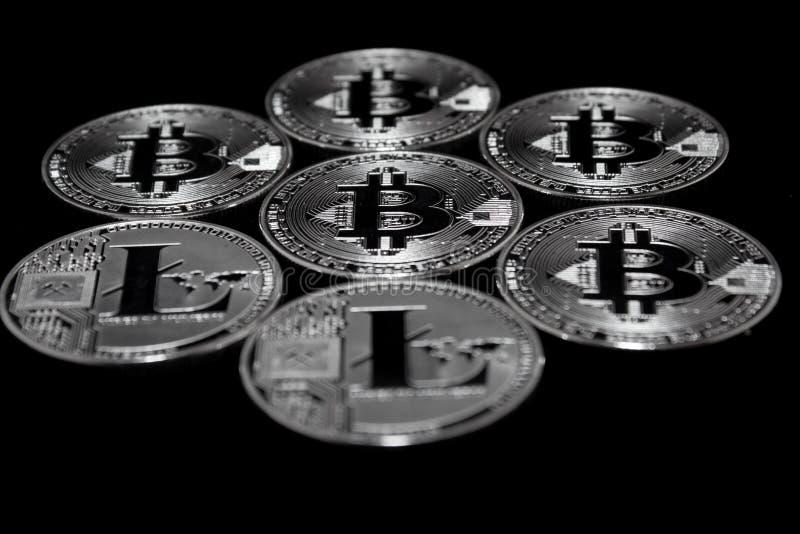 Bitcoin y litecoin Crypto de las monedas en un fondo negro foto de archivo libre de regalías