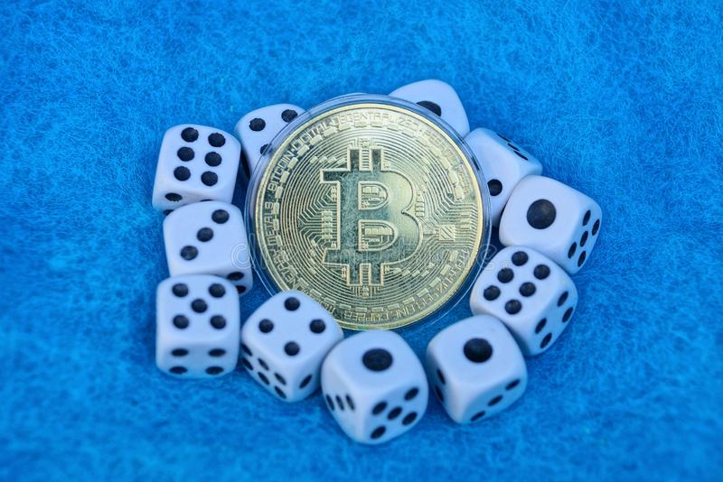Bitcoin yellow coin and white game dice on blue wool royalty free stock photography