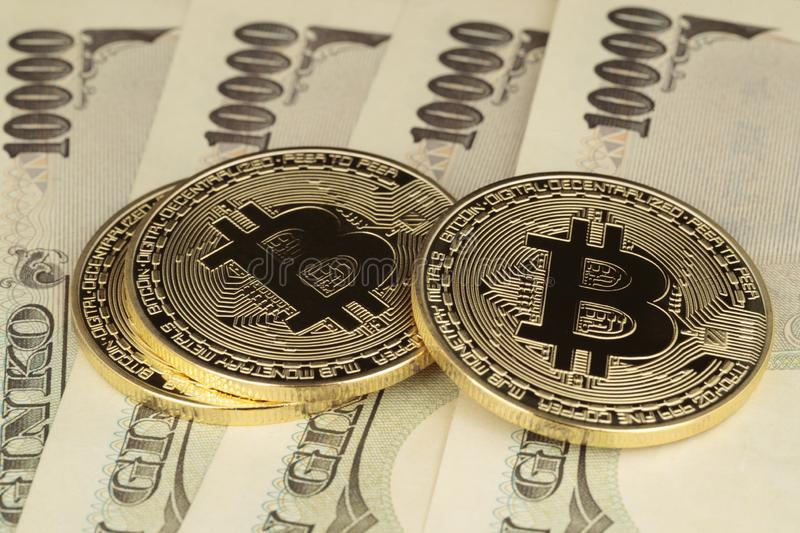 Three Bitcoins and Yen bills stock images