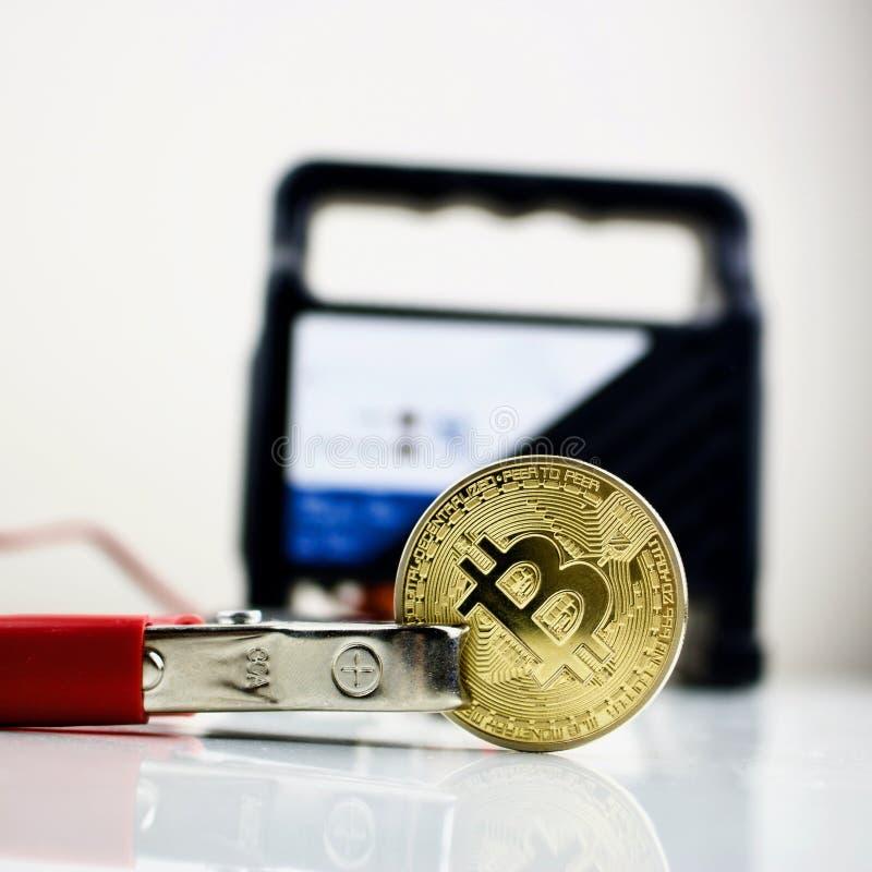 Bitcoin złocista moneta i samochodowa bateryjna ładowarka zdjęcie royalty free