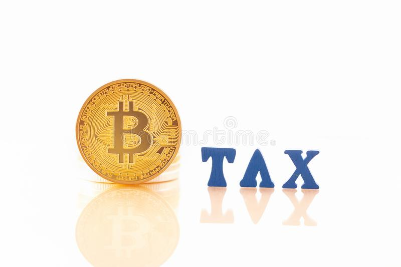 BitcoinBTC coin gold and wooden letters TAX on white background. stock images