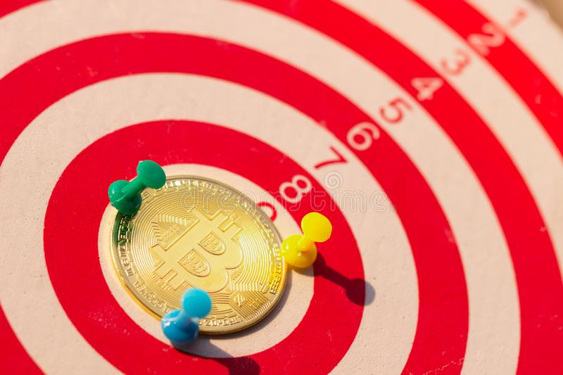 BitcoinBTC Gold and Darts arrow hitting in the target center of dartboard. royalty free stock image