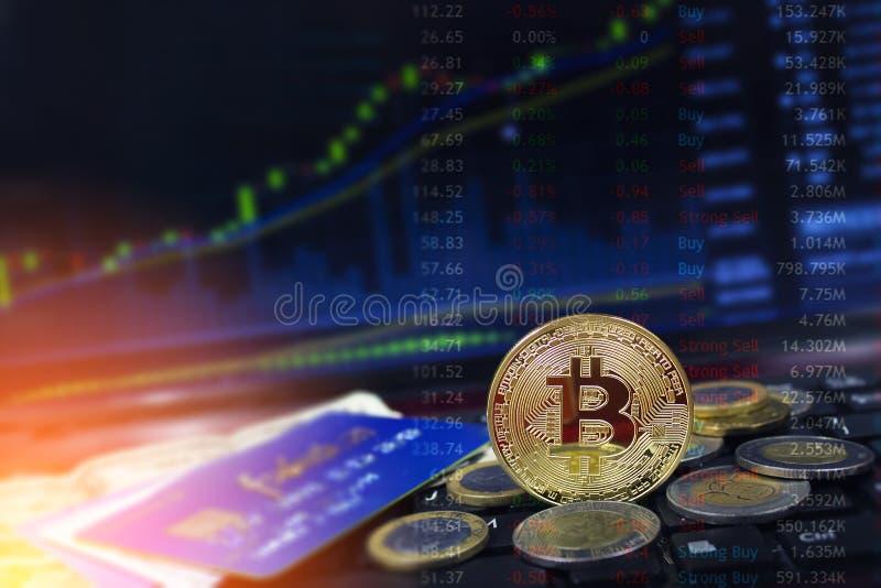 Bitcoinmunt met creditcards en muntstukken op laptop toetsenbord met het toenemen prijsgrafieken op de achtergrond stock foto