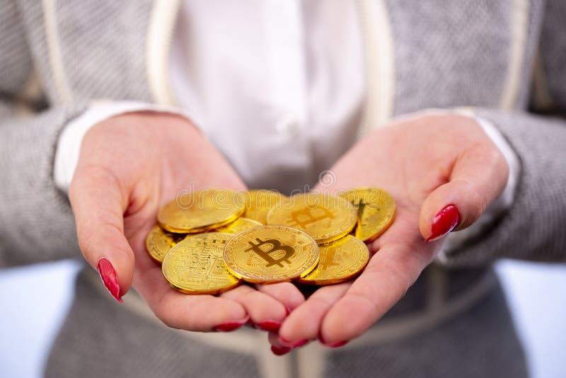 Bitcoinmuntstuk in de handen van de vrouw stock foto's