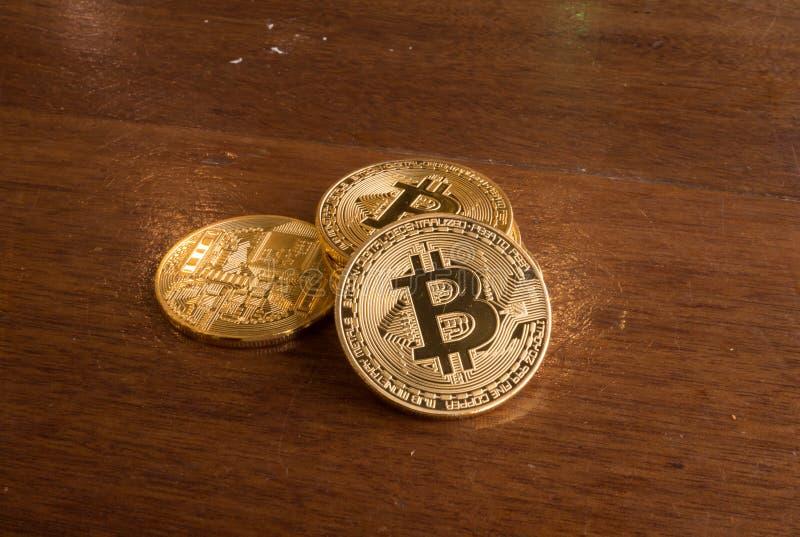 Bitcoinmuntstuk die zich op een bruine lijst bevinden stock foto's