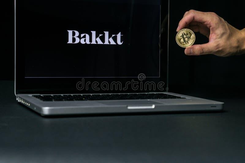 Bitcoinmuntstuk met het Bakkt-embleem op het laptop scherm, Slovenië - December 23th, 2018 stock foto