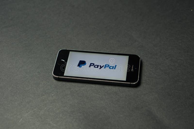 Bitcoinmuntstuk met het Paypal-embleem op het telefoonscherm, Slovenië - December 23th, 2018 stock afbeelding