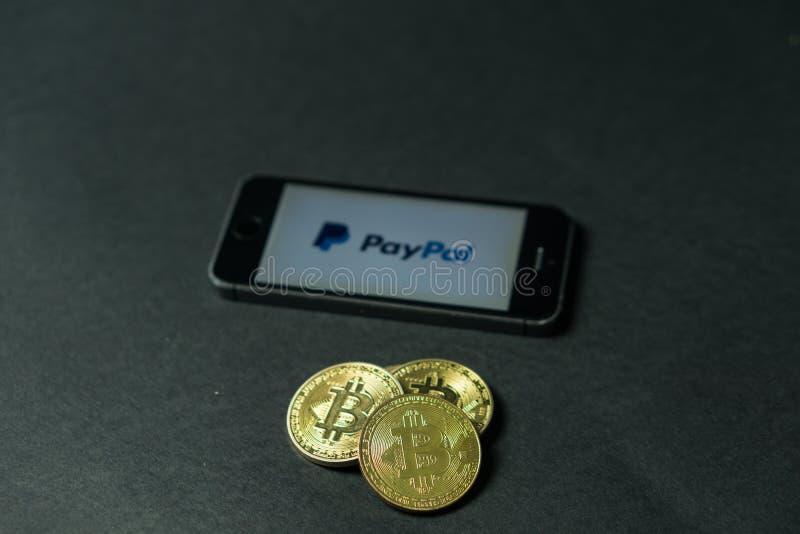 Bitcoinmuntstuk met het Paypal-embleem op het telefoonscherm, Slovenië - December 23th, 2018 stock fotografie