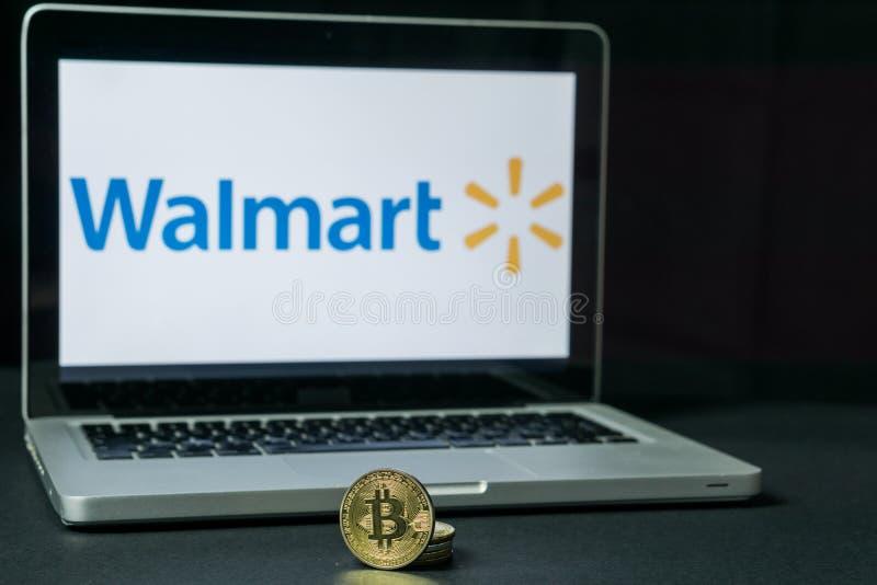 Bitcoinmuntstuk met het Walmart-embleem op het laptop scherm, Slovenië - December 23th, 2018 royalty-vrije stock afbeelding