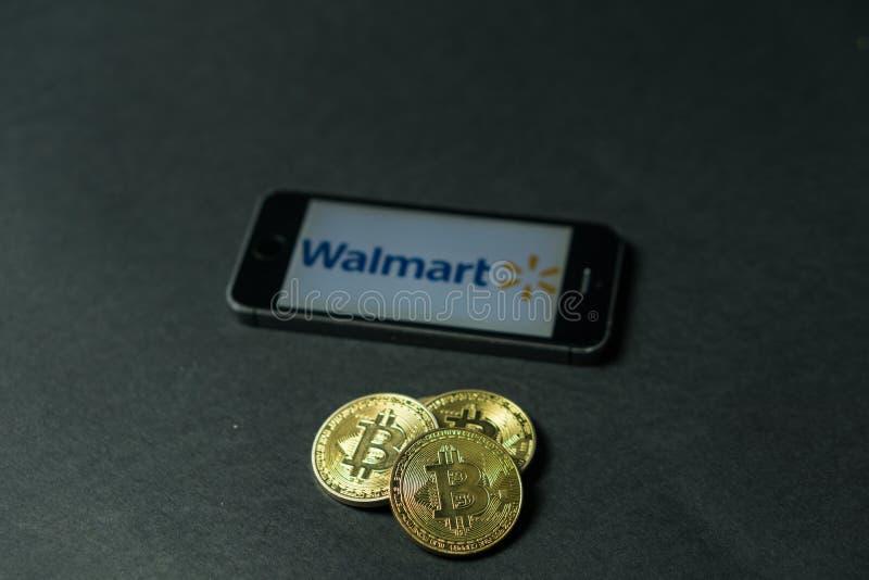 Bitcoinmuntstuk met het Walmart-embleem op het telefoonscherm, Slovenië - December 23th, 2018 stock afbeeldingen