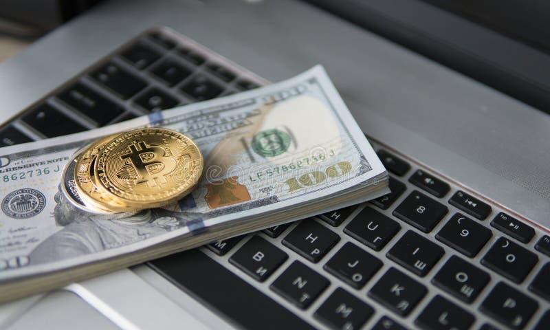Bitcoinmuntstuk met laptop en ons dollars Bitcoin gouden muntstukken op het bureau van dollarbankbiljetten witte laptop als achte royalty-vrije stock afbeeldingen