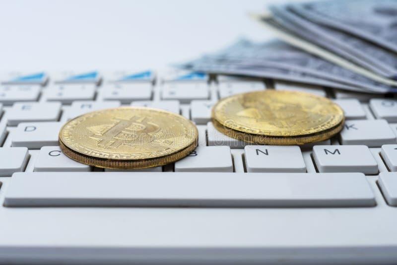 Bitcoinmuntstuk met toetsenbord en Amerikaanse dollars Bitcoin gouden muntstukken op het bureau van dollarbankbiljetten met een w stock foto's