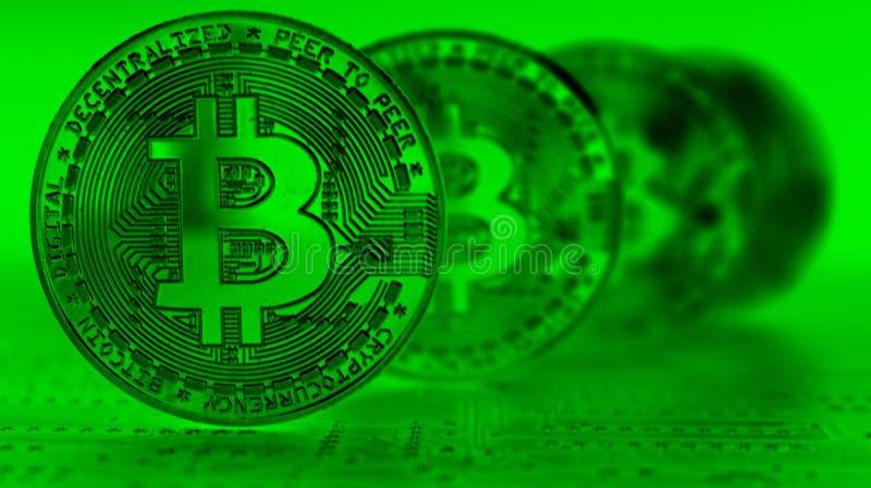 4 Bitcoins与在前面硬币的焦点在绿色色彩 图库摄影