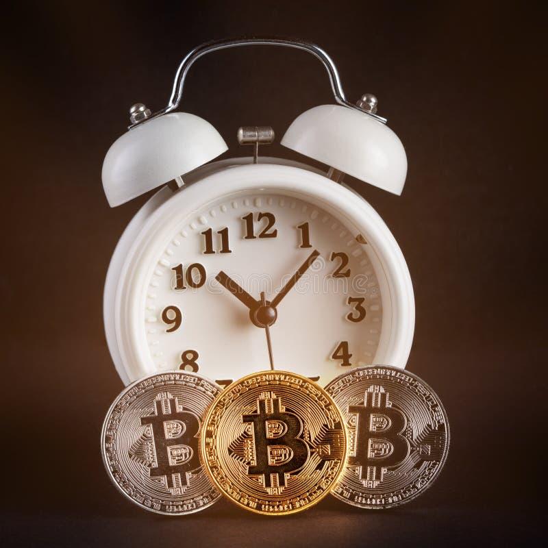 3 bitcoins и винтажного белого будильник накаляя на черной предпосылке стоковая фотография