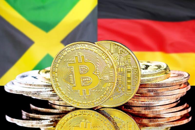 Bitcoins auf Jamaika- und Deutschland-Flagge Hintergrund stockbilder