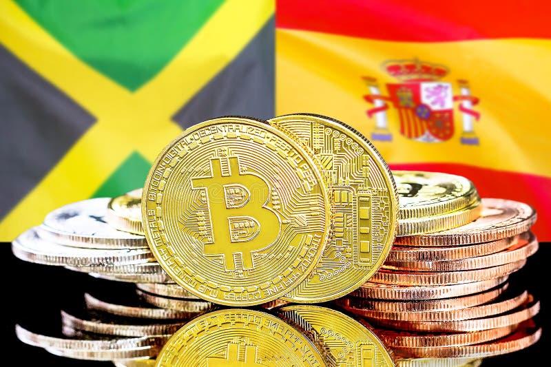 Bitcoins auf Jamaika- und Spanien-Flagge Hintergrund stockbilder