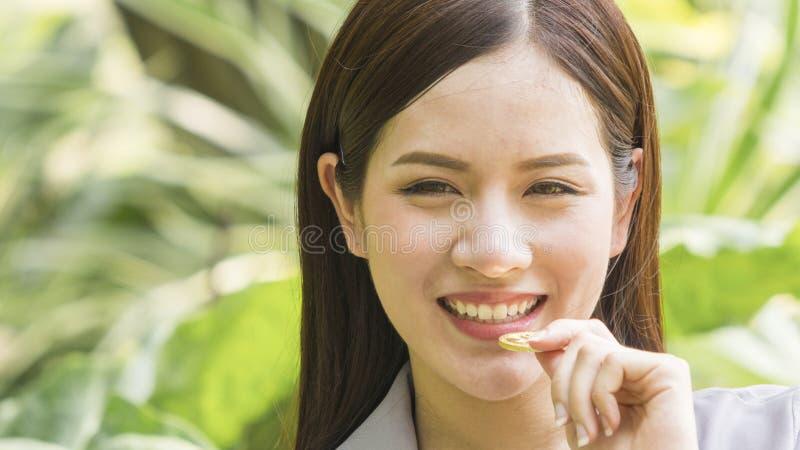 Bitcoins - Bitcoin à disposition d'une prise occasionnelle de femme d'affaires de sourire photo stock