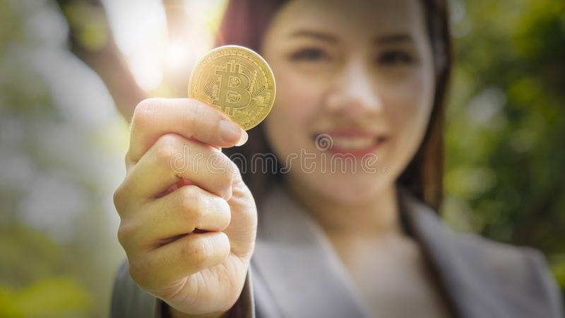 Bitcoins - Bitcoin in hand of a casual businesswoman to show the royalty free stock image