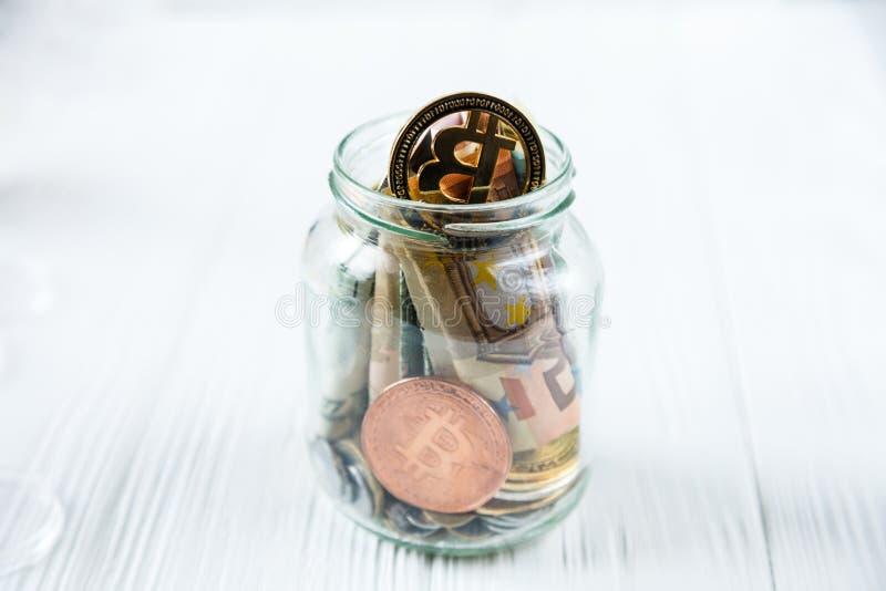 Bitcoins brązowa złota moneta w szklanym słoju na białym drewnianym stole Set cryptocurrencies z istnym euro, dolary w słoju fotografia stock