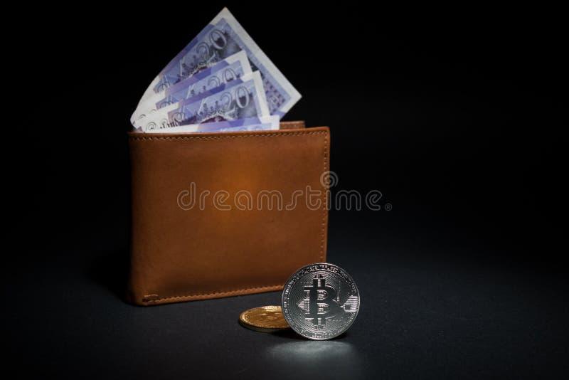 Bitcoins cerca de la cartera con las libras inglesas foto de archivo
