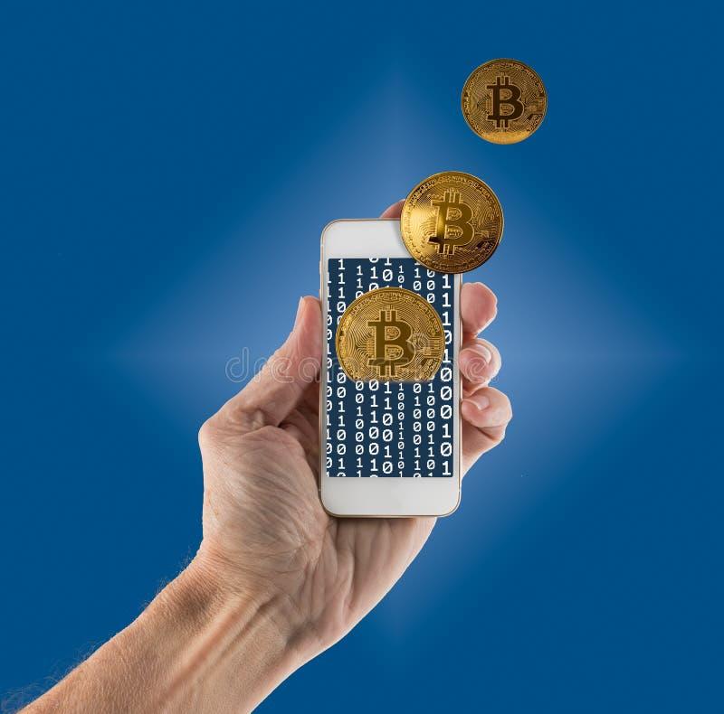 Bitcoins che emerge dal app sullo smartphone tenuto in mano fotografie stock libere da diritti