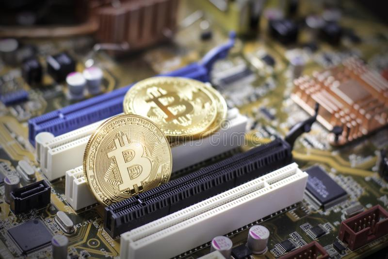 Bitcoins on the computer motherboard. Mining cryptocurrency royalty free stock image