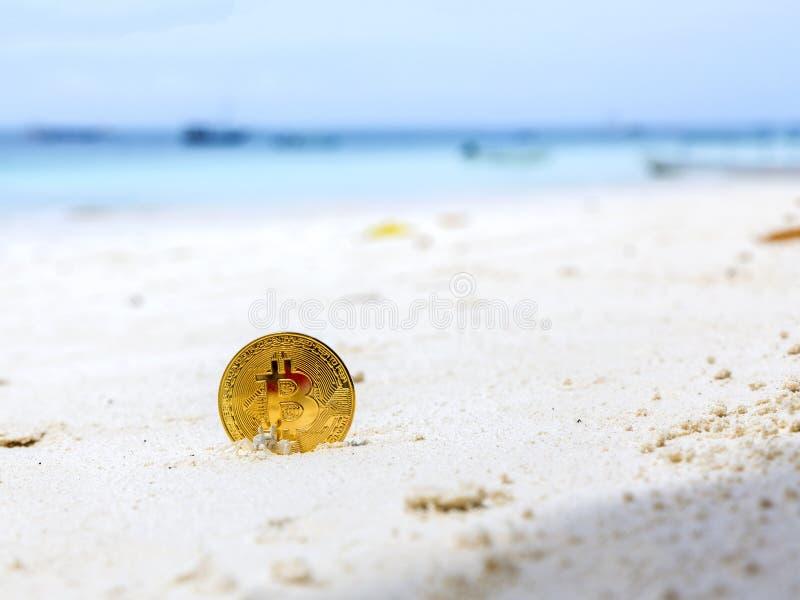 Bitcoins d'or sur un sable de plage photos stock