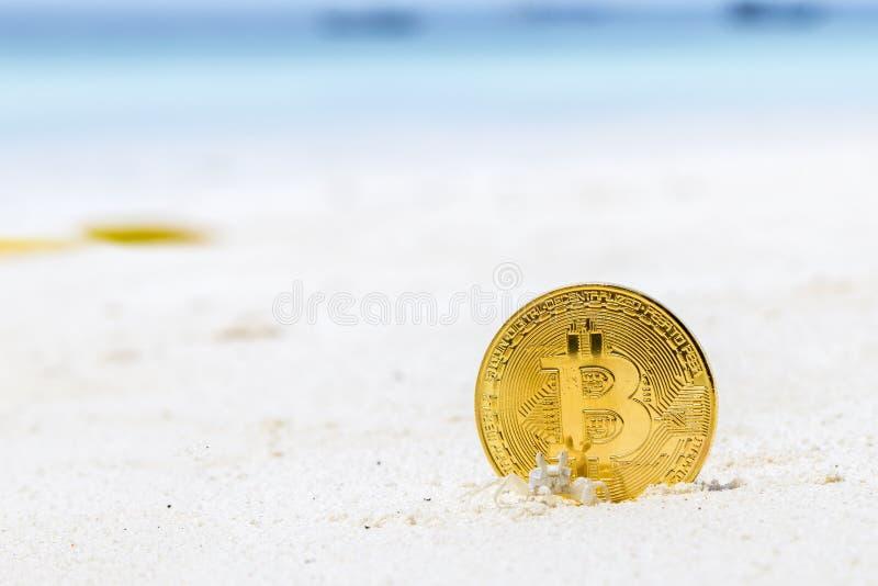 Bitcoins d'or sur un sable de plage images stock