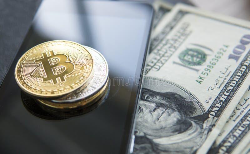 Bitcoins de oro en el teléfono y dólar elegantes con el cuaderno en fondo Currebcy crypto de Bitcoin Moneda de Digitaces foto de archivo