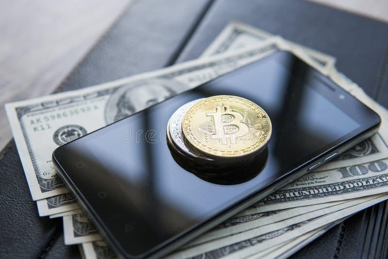 Bitcoins de oro en el teléfono y dólar elegantes con el cuaderno en fondo Currebcy crypto de Bitcoin Moneda de Digitaces fotos de archivo libres de regalías