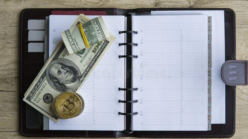 Bitcoins de oro en el top y en dólar y cuaderno Currebcy crypto de Bitcoin en dólares de EE. UU. Dinero virtual Metal foto de archivo libre de regalías