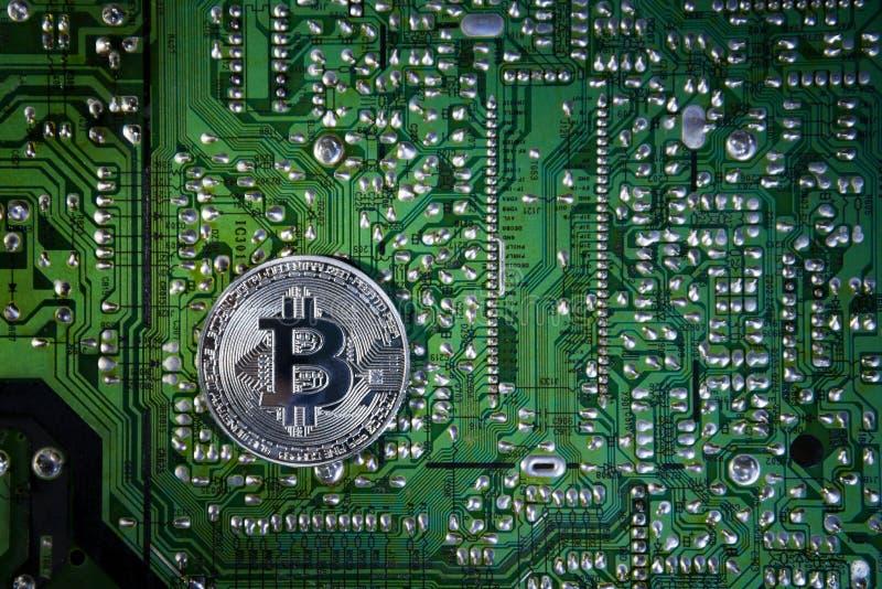 Bitcoins de plata en el microprocesador El fondo verde Cripta de la seguridad fotografía de archivo libre de regalías