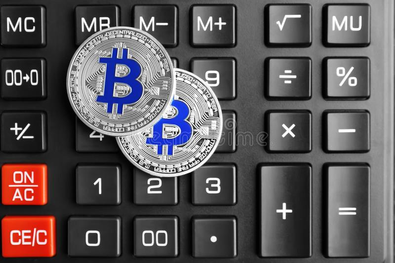 Bitcoins de prata na calculadora foto de stock royalty free