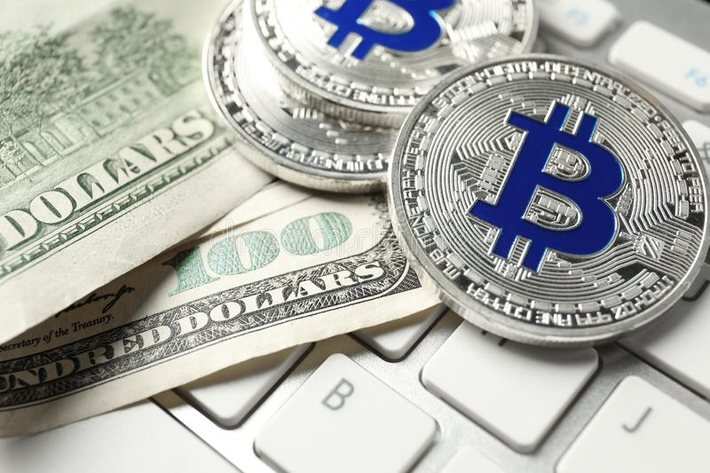 Bitcoins and dollar banknotes on PC keyboard, closeup stock photos