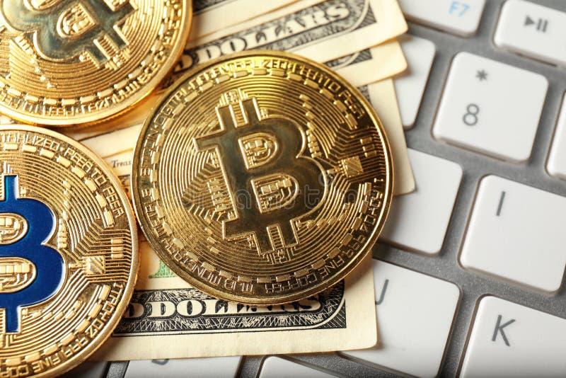 Bitcoins and dollar banknotes on PC keyboard, closeup royalty free stock photo