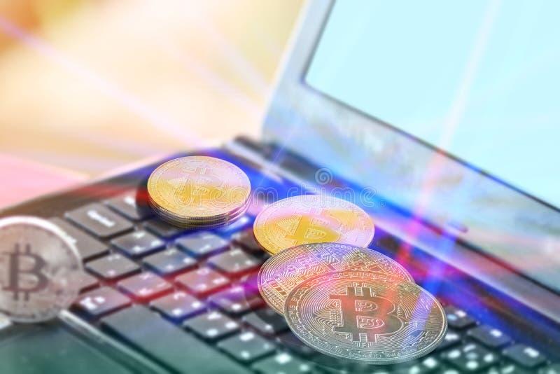 Bitcoins dorati sul computer della tastiera e soldi virtuali della fabbrica leggera sui nuovi fotografia stock
