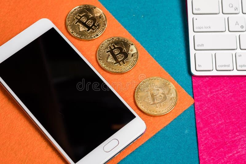 Bitcoins dourados em uma parte superior, e telefone e portátil espertos fotografia de stock