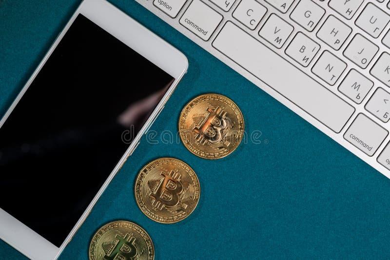 Bitcoins dourados em uma parte superior, e telefone e portátil espertos fotos de stock