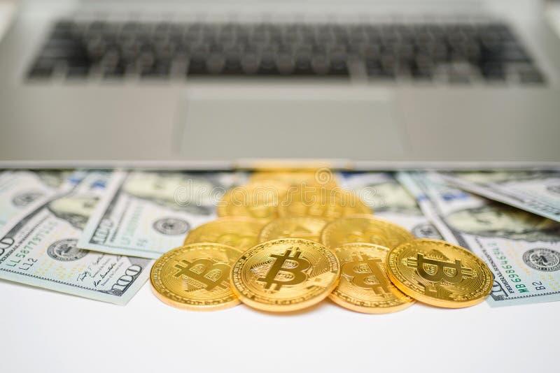 Bitcoins e banconote in dollari che compaiono da sopra il computer portatile fotografia stock